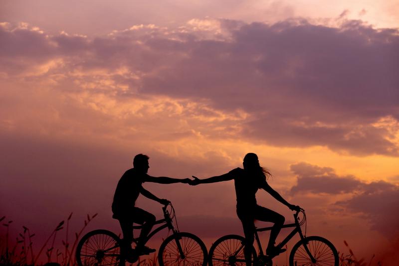 femme et homme sur des vélos se tendent la main