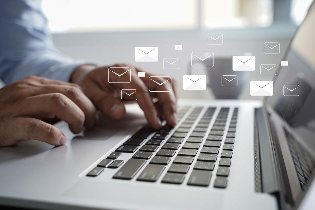 mains tapotant sur un clavier d'ordinateur pour rédaction d'un email