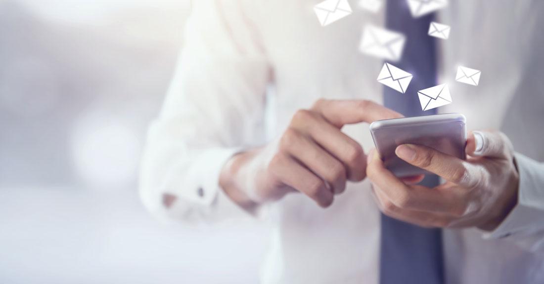 personne utilisant son smartphone pour envoyer des mails